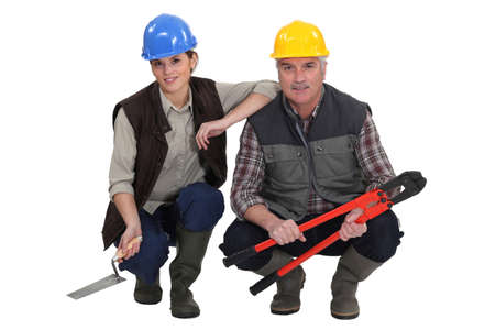 kneeled: Two kneeled construction workers.