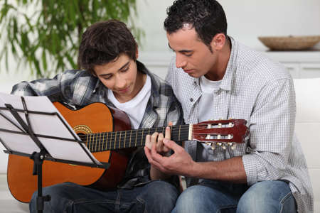 Father teaching son the guitar photo