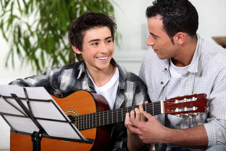 Father and son with acoustic guitar photo