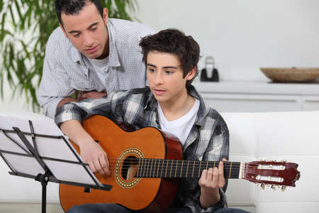 practise: Adolescent boy learning to play the guitar Stock Photo