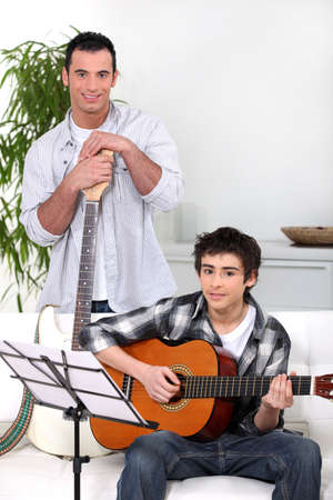 playing the guitar: Man teaching teenage boy the guitar
