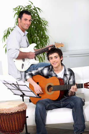 Father teaching son how to play the guitar photo