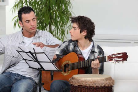 teaching music: Father and son with a guitar