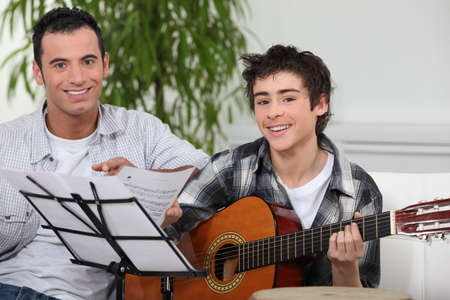 teaching music: Adolescent boy learning to play the guitar Stock Photo