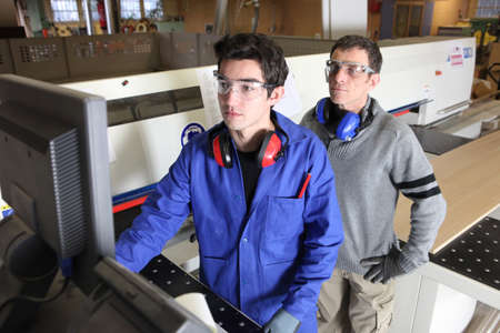 forestry industry: Young intern operating factory saw