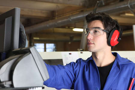 Young man operating machine in factory photo