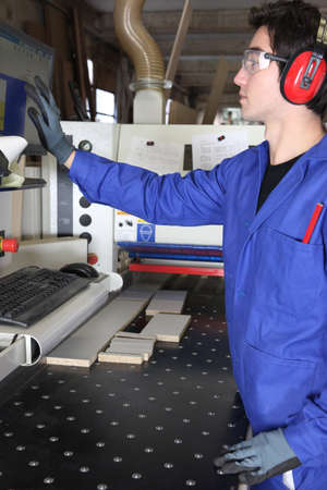machinetool: Young worker operating factory machine
