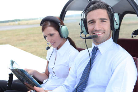 Smiling man sitting in the cockpit of a light aircraft as his partner consults a mapbook photo