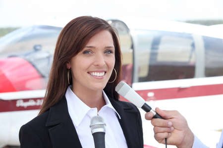 feat: Woman interviewed in front of airplane Stock Photo