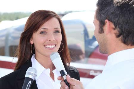 reportero: Reportero entrevistando a la mujer en el aeropuerto