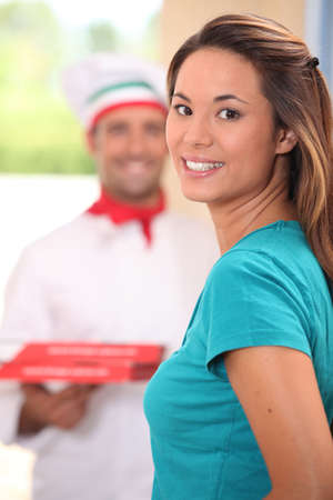 Delivery man bringing pizzas to young woman photo