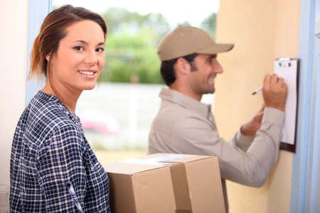 cartero: Una mujer recibe un paquete Foto de archivo