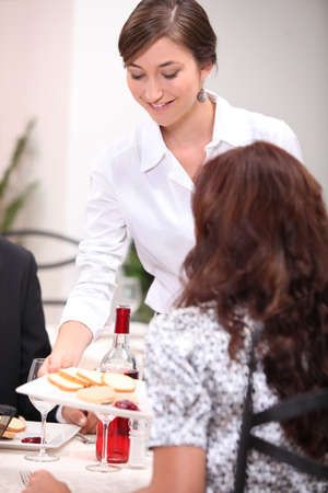 alcohol server: Waitress serving a pate starter in a restaurant