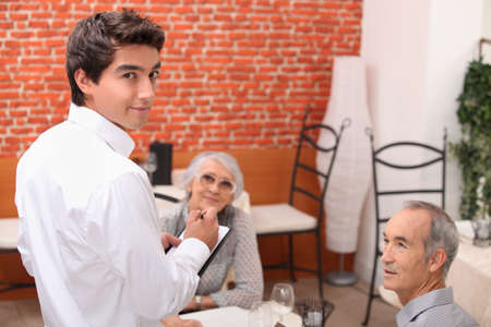 mature couple at restaurant with waiter photo