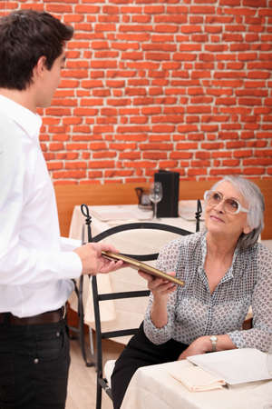 mature lady being served by waiter at restaurant photo