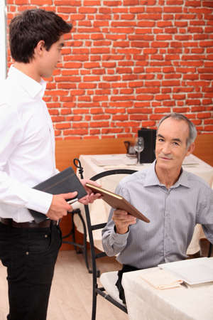 Waiter proposing menu to client photo
