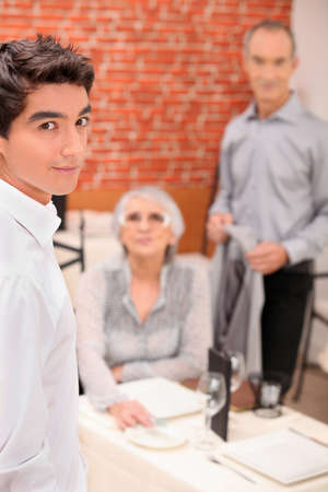 Young waiter serving an older couple in a restaurant photo