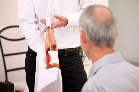 client service: Waitress serving wine in a restaurant