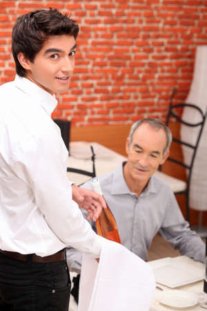 Waiter serving a bottle of rose to a male diner in a restaurant Stock Photo