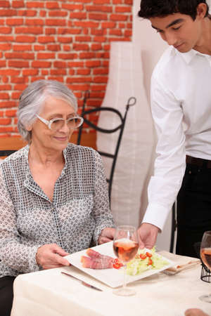 dining out: Young waiter serving lunch to an older customer Stock Photo