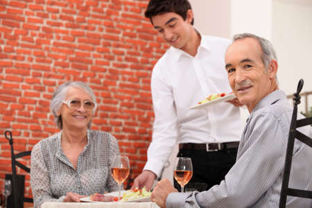 Old couple having meal in restaurant photo
