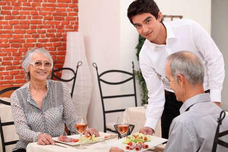 alcohol server: Waiter serving a senior couple Stock Photo