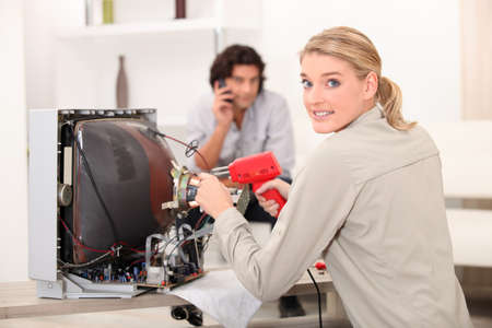 Woman repairing television with soldering iron Stock Photo - 13841695