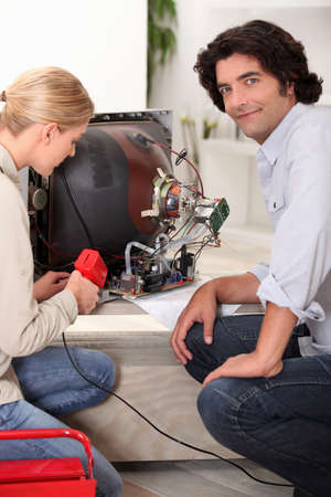 Couple repairing old television together photo
