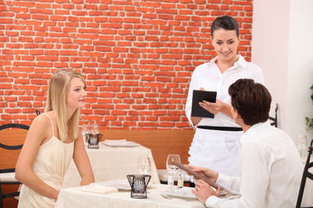 Couple ordering food in restaurant photo