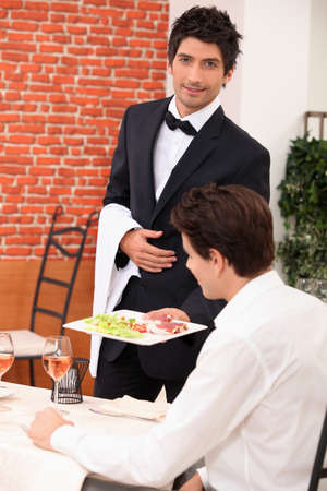 Waiter deliver in meal in restaurant photo