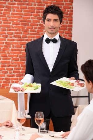 alcohol server: Waiter delivering meals to table