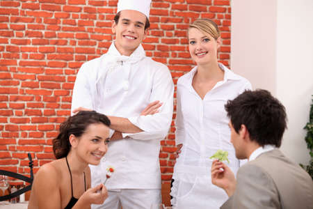 a couple dining at restaurant, a cook and a waitress behind them Stock Photo