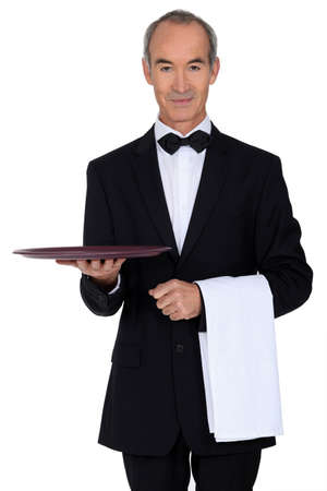 Senior waiter holding empty tray photo
