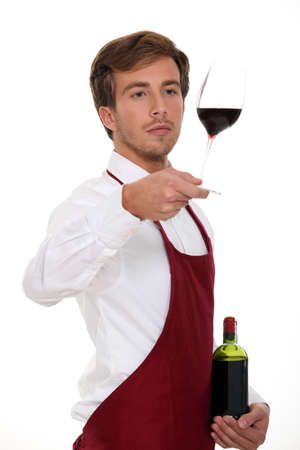 Sommelier holding up a glass of wine photo