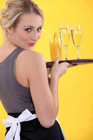 Attractive waitress serving drinks photo