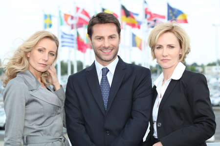 fair hair: Business people in front of flags Stock Photo