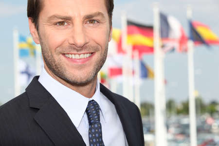 managerial: Excecutive in front of flags Stock Photo