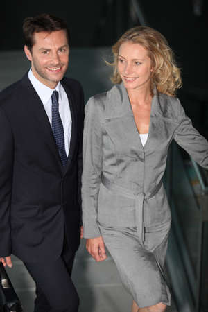 Executive couple walking down a ramp photo