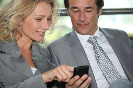 parter: Pair of executives looking at something on a cellphone Stock Photo
