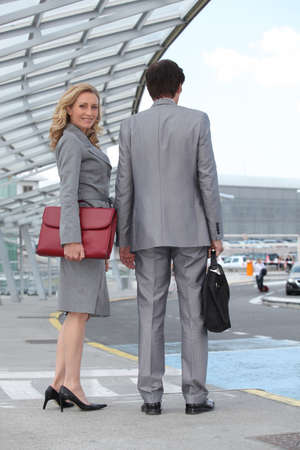 tailor suit: Executive couple waiting for taxi Stock Photo