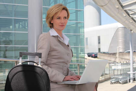 Businesswoman on laptop outside airport photo