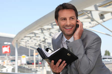 Businessman on phone with diary photo