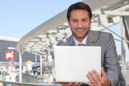 laptop outside: Businessman with laptop outside.