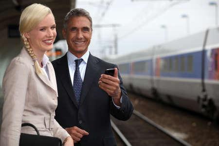 confidant: portrait of handsome mature businessman and young female assistant