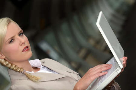 serious woman wearing a beige suit is working on her laptop in a dark tunnel Stock Photo - 13841715