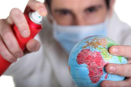 Man spraying an aerosol over planet earth photo