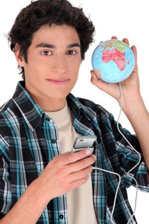 dospívající chlapec drží mobilní telefon připojený k zeměkoule