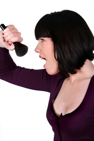 Woman singing into a make-up brush photo