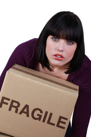 Woman carrying a heavy box marked fragile Stock Photo - 13844250