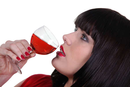 Striking shot of a woman drinking a glass of wine photo